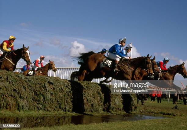 Horseracing action at the Water Jump during the Grand National at Aintree on 8th April 1989 Far right Little Polveir ridden by Jimmy Frost the...