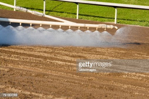 Horseracing track being sprayed with water : Foto de stock