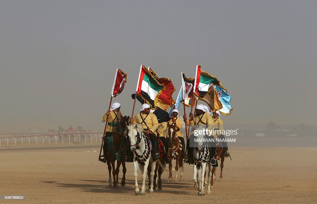 Horse-riders take part in the Sheikh Sultan Bin Zayed al-Nahyan herithe festival, held at the Shweihan racecourse in Al-Ain, on the outskirts of Abu Dhabi, on February 12, 2016. The festival includes a camel beauty contest, a traditional souq, a camel auction, and competitions for traditional handicrafts. / AFP / MARWAN NAAMANI