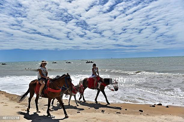 Horseriders travel along a beach of Cumbucu near Fortaleza on June 23 during the 2014 FIFA World Cup AFP PHOTO / ARIS MESSINIS