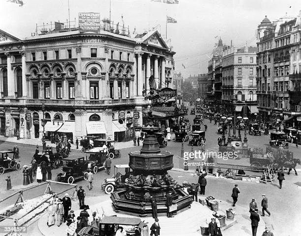 Horses and carts travelling through Piccadilly Circus central London alongside cars
