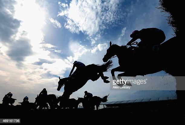 Horses and riders clear a fence during the Betfred Mildmay Novices' Steeple Chase at Aintree Racecourse on April 10 2015 in Liverpool England