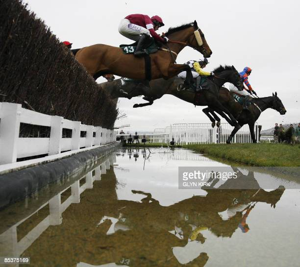 Horses and riders clear an obstacle during The 139th Year Of The National Hunt Steeple Chase Challenge Cup on the second day of the Cheltenham...