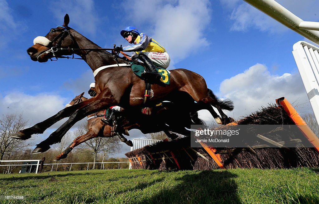 Horses and riders jump a fence during the Ben Burgess Novices Handicap Hurdles Race on February 15, 2013 in Fakenham, England.