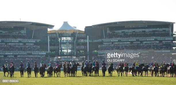 Horses and riders line up to start the Grand National horse race on the final day of the Grand National Festival horse race meeting at Aintree...