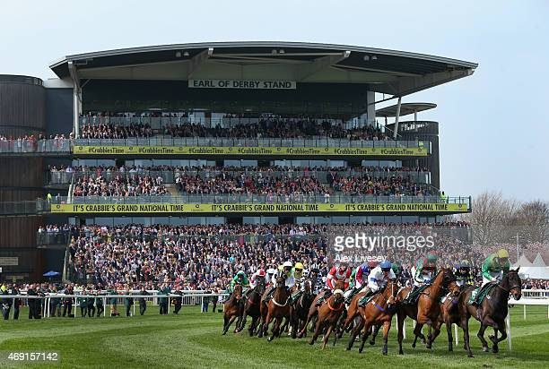 Horses and riders pass the grandstands during the Alder Hey Children's Charity Handicap Hurdle Race at Aintree Racecourse on April 10 2015 in...