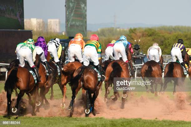 Horses and riders race during the Grand National horse race on the final day of the Grand National Festival horse race meeting at Aintree Racecourse...