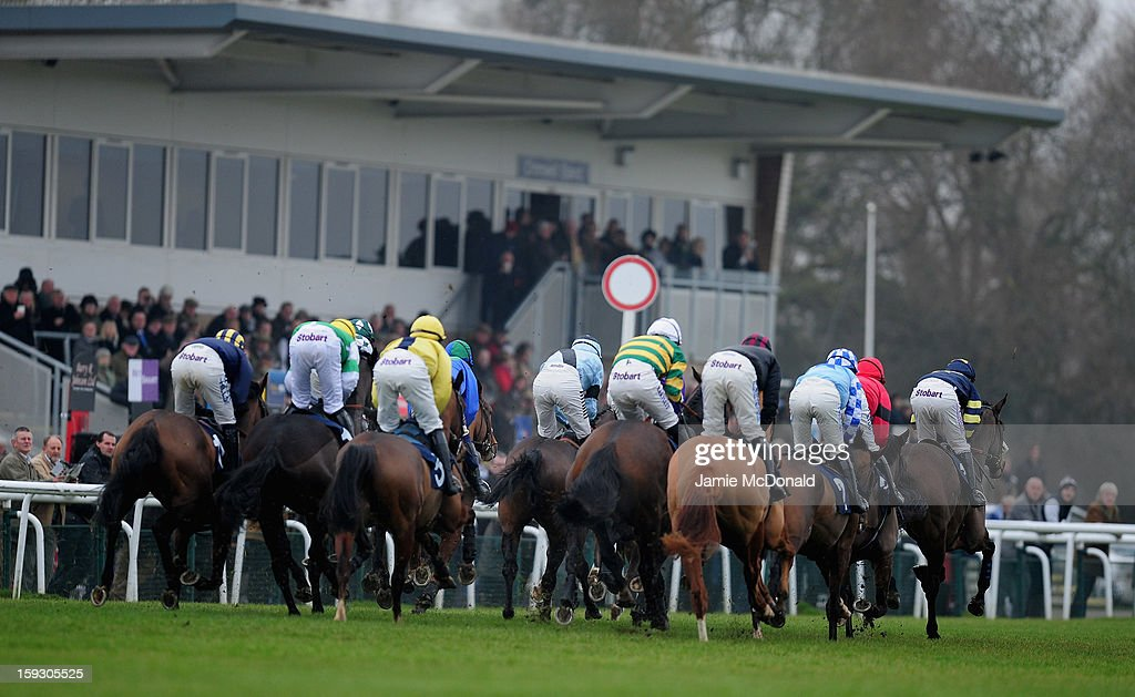 Horses and rides pass the grand stand during the Connoll's Red Mills National Hunt Novices Hurdle Race at Huntingdon Racecourse on January 11, 2013 in Huntingdon, England.