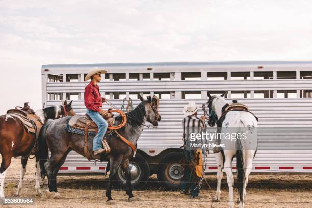 horses and their riders by the trailer