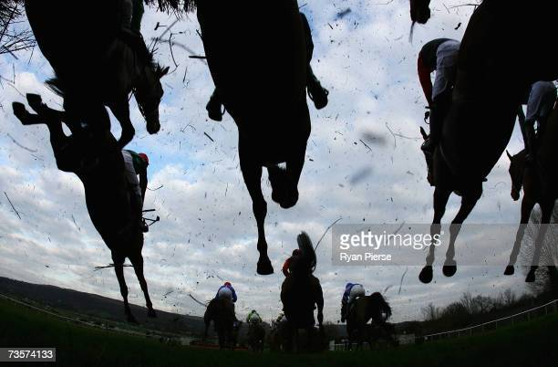 Horses clear a jump during the Challenge Cup Handicap Steeple Chase on the second day of The Annual National Hunt Festival held at Cheltenham...