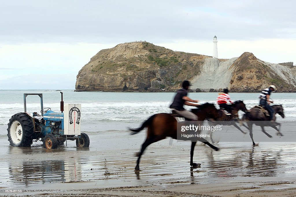 Horses cross the finish line in the Wairarapa Station Hack Race during the Castlepoint Beach Races at Castlepoint Beach on March 2, 2013 in Masterton, New Zealand.