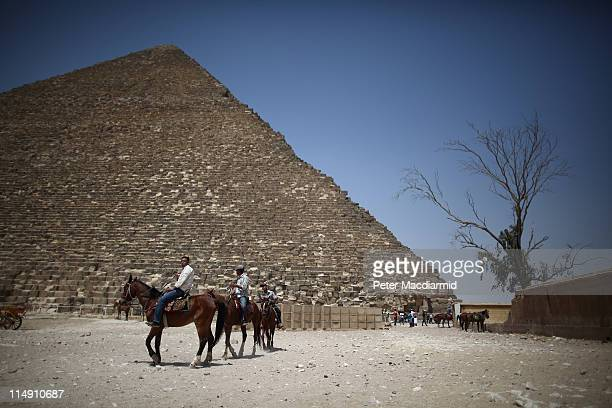 Horses for tourists pass near the great Pyramid of Cheops on May 28 2011 in Giza Egypt Protests in January and February brought an end to 30 years of...