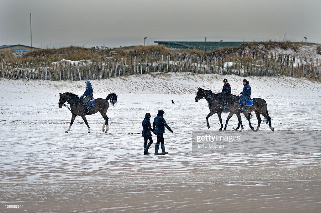 Horses make their way across St Andrew beach on January 18, 2013 in St Andrews, Scotland. Widespread snowfall is affecting most of the UK with school closures and transport disruption. The Met Office has issued a red weather warning for parts of Wales, advising against all non-essential travel as up to 30cm of snow is expected to fall in some areas today.