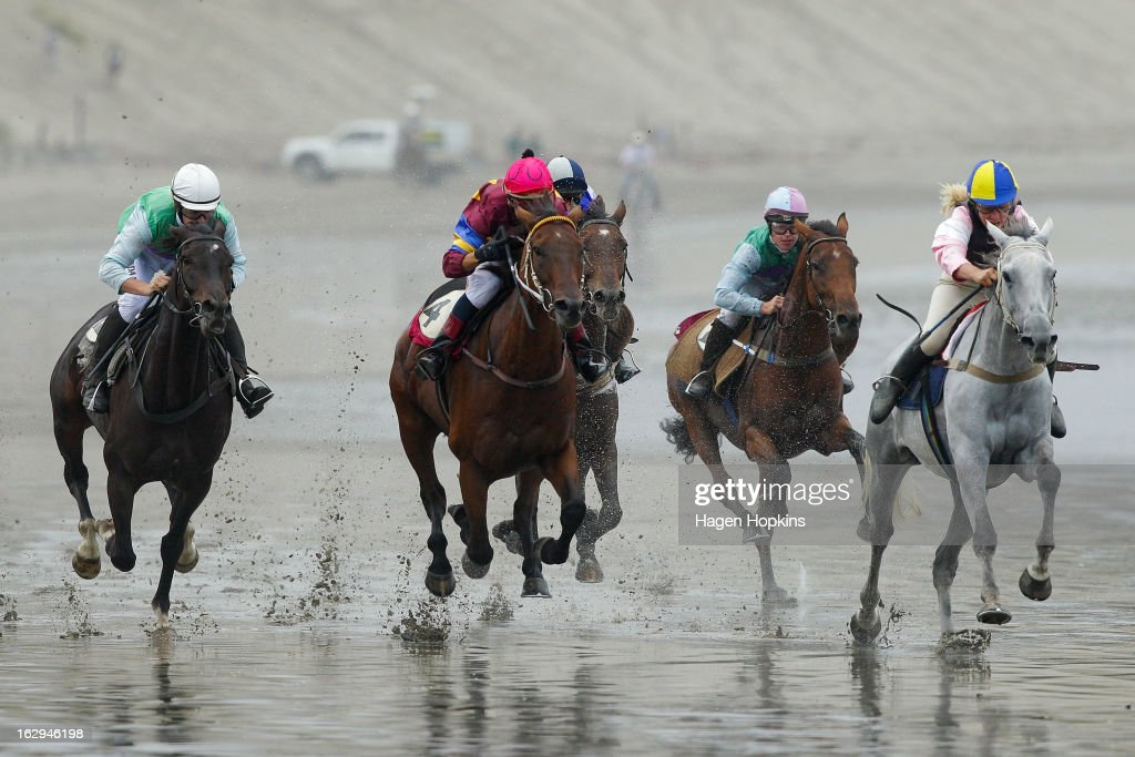 Horses race in the Tinui Highweight Handicap Open during the Castlepoint Beach Races at Castlepoint Beach on March 2, 2013 in Masterton, New Zealand.