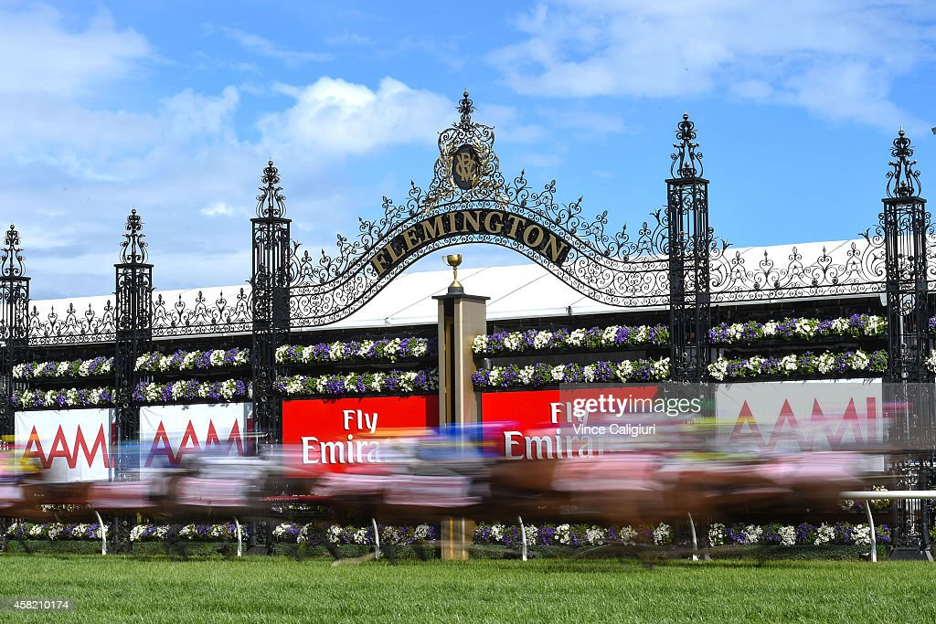 Horses race past the post in the first lap of Race 7 the AAMII Victoria Derby during Derby Day at Flemington Racecourse on November 1 2014 in...