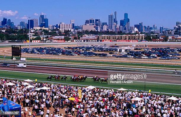 Horses racing at Flemington Race Course & city skyline.
