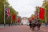 Horses ride down The Mall which is lined with The British Union Jack flag and the Chinese Wu Xing Hong Qi flag ahead of the Chinese State Visit on...