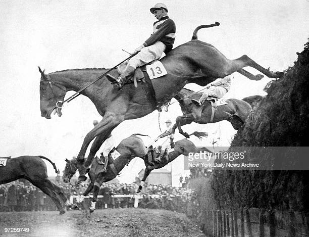 Horses take Beecher's Brook jump in the Grand National Steeplechase at Aintree England