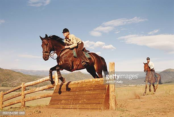 Horsewoman and horseman jumping cross-country fence , side view