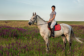Horsewoman jockey in uniform riding horse outdoors. Sunset. Horseback Riding. Competition. Hobby