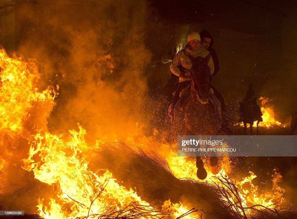 A horsewoman jumps over a bonfire in the central Spanish village of San Bartolome de Pinares to open the celebrations for the feast of Saint Anthony, patron saint of animals, on January 16, 2013.