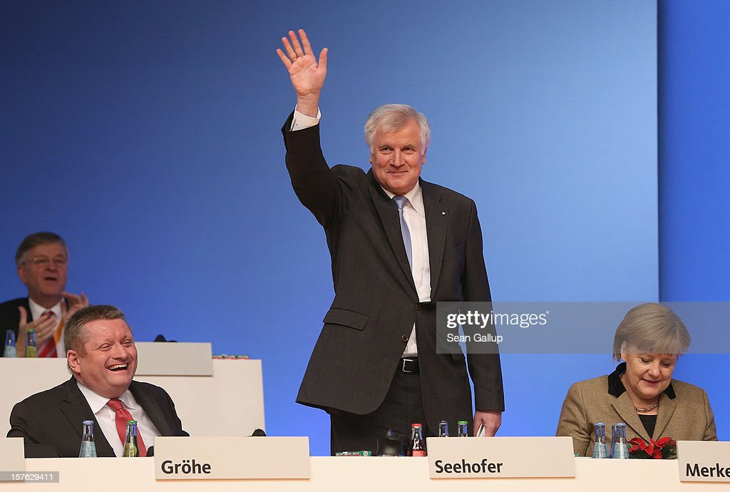 Horst Seehofer, Chairman of the Christian Social Union (CSU), the Bavarian sister party of the German Christian Democratic Union (CDU), waves to delegates after he spoke at the CDU federal party convention as CDU General Secretary Hermann Groehe (L) and German Chancellor and CDU Chairwoman Angela Merkel look on on December 5, 2012 in Hanover, Germany. The CDU has a strong lead over its opponents though has recently lost the mayoral posts in several major German cities to opposition parties. Germany faces federal elections in 2013.