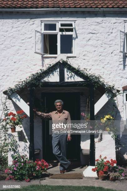 Horticulturist and broadcaster Clay Jones stands near a cottage's doorway 1983