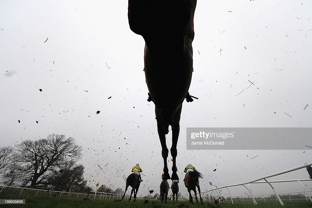 Hoses and riders over the ditch during the Connoll's Red Mills Horescare Cubes Novices Steeple Chase at Huntingdon Racecourse on January 11, 2013 in Huntingdon, England.