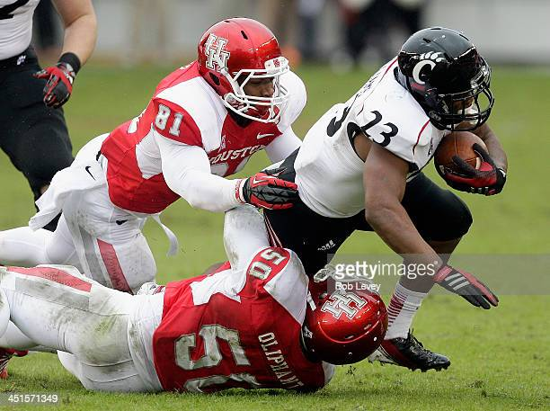Hosey Williams of the Cincinnati Bearcats is tackled by Tyus Bowser of the Houston Cougars and Efrem Oliphant at BBVA Compass Stadium on November 23...
