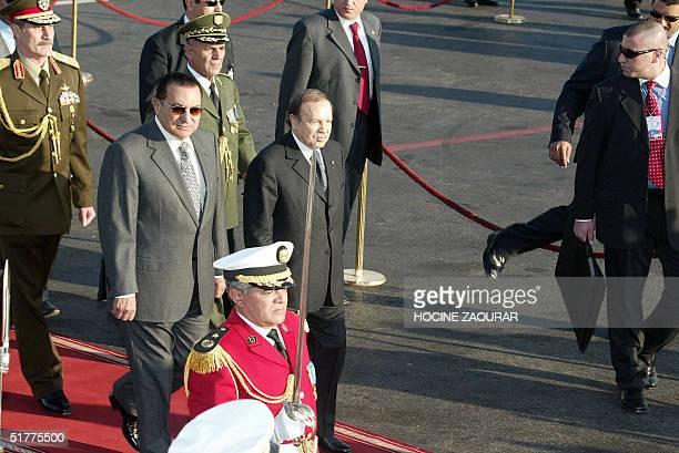 Hosni Mubarak Egyptian president is accompanied by his Algerian counterpart Abdelaziz Bouteflika upon his arrival 22 November 2004 at Algiers airport...
