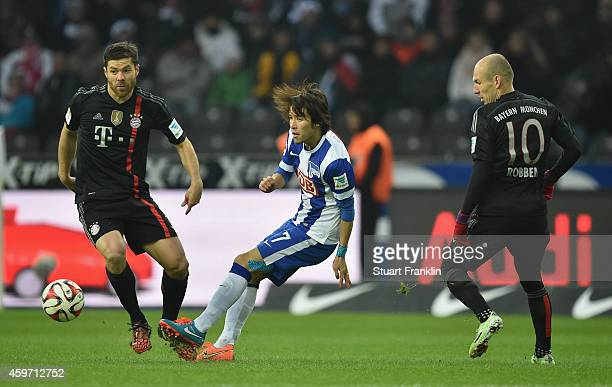 Hosogai Haijme of Berlin challenges Arjen Robben and Xabi Alonso of Muenchen during the Bundesliga match between Hertha BSC and FC Bayern Muenchen at...