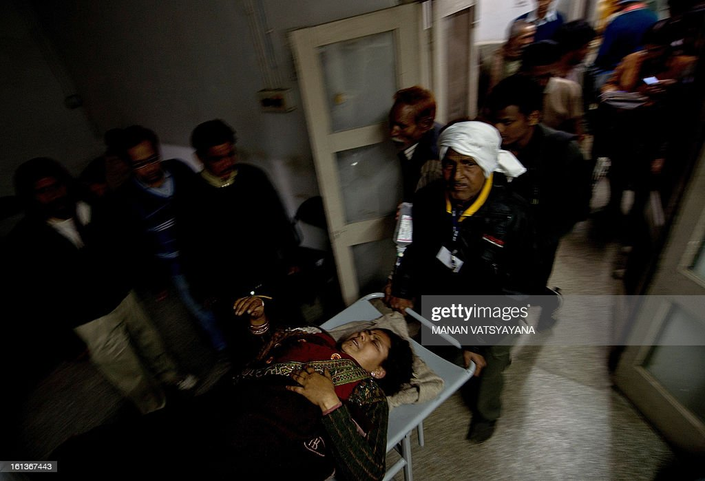 Hospital attendants carry an Indian woman injured in the stampede at the Railway Hospital in Allahabad on February 10, 2013. At least 10 people died in the stampede as pilgrims headed home from India's giant Kumbh Mela festival, which drew a record 30 million people to the banks of the river Ganges. The lives were lost at the main railway station where 10 corpses wrapped in white sheets could be seen on a train platform several hours after the incident which occurred in the early evening, an AFP photographer said.