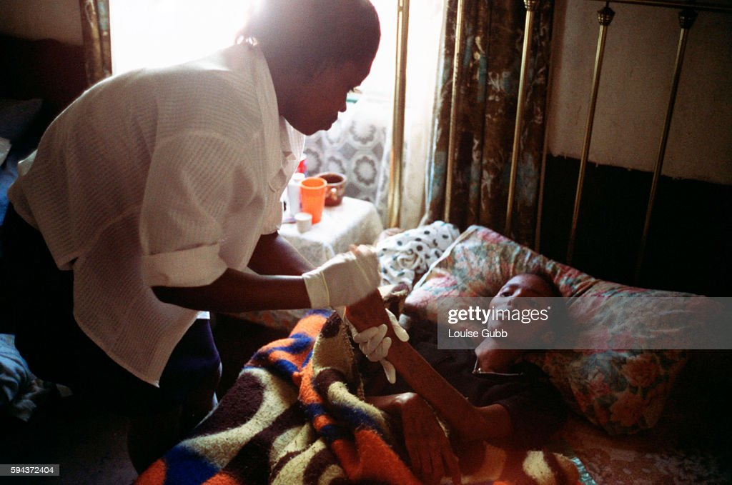 Hospital caregiver makes her first visit to Pumzile age 20 who has contracted AIDS and is now bedridden has partial paralysis in the legs and has raw...