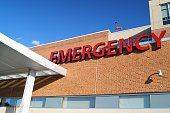 A red Emergency sign marks the entrance of a hospital emergency department
