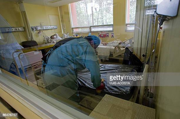 A hospital employee cleans a bed inside a room for patients presenting symptoms of the swine flu virus now named influenza A kept in isolation at the...