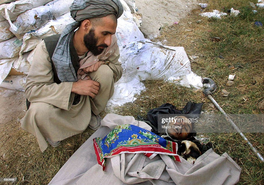 Hospital guard Mohammed Abraham looks at the body of a suspected al Qaeda fighter at Mir Wais Hospital January 8 2002 in Kandahar Afghanistan The...