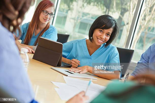 Hospital interns, nurses, and doctors having staff meeting
