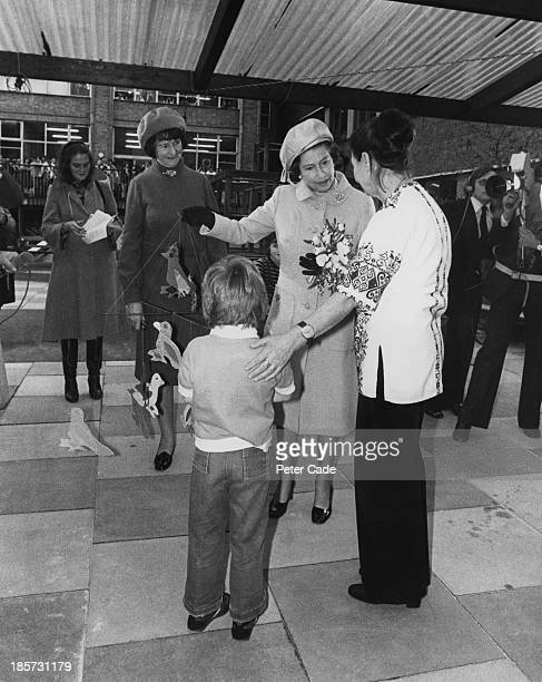 Hospital patient David Holmes presents a mobile made by him and fellow patients to Queen Elizabeth II during her visit to Great Ormond Street...