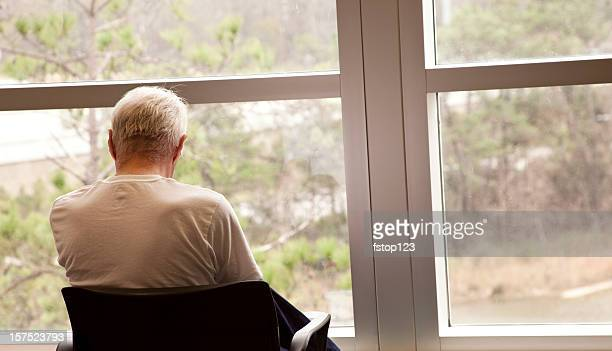 Hospital patient waiting by a window. Senior adult man. Depression.