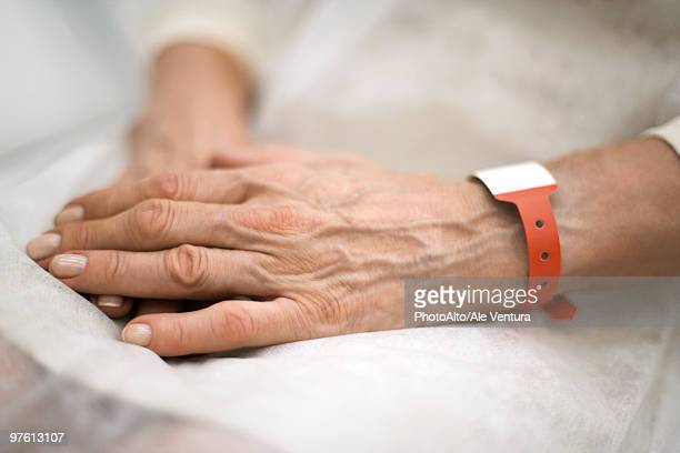 Hospital patient's hands folded in lap, close-up