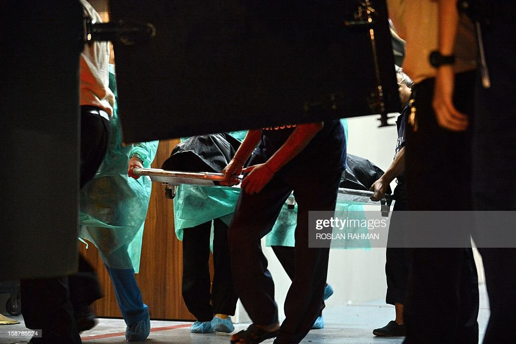 Hospital staff carry the body of the Indian gang-rape victim to the police morgue vehicle at the Mount Elizabeth hospital in Singapore on December 29, 2012. The victim, 23, died Saturday in Singapore after suffering severe organ failure, the hospital treating her said, in a case that sparked widespread street protests over violence against women. AFP PHOTO/ROSLAN RAHMAN