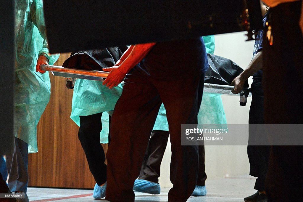 Hospital staff carry the body of the Indian gang-rape victim to the police morgue vehicle at the Mount Elizabeth hospital in Singapore on December 29, 2012. The 23-year-old woman died Saturday in Singapore after suffering severe organ failure, the hospital treating her said, in a case that sparked widespread street protests over violence against women.
