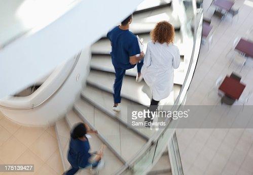 Hospital staff climbing spiral steps : Stock Photo