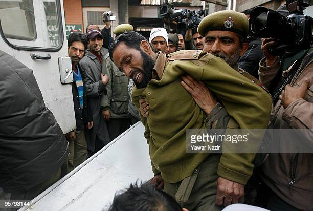 Hospital staff members carry a wounded Indian policeman on a gurney from an ambulance to a hospital on January 15 2010 in Srinagar India Two people...
