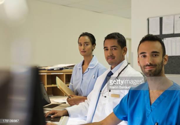 Hospital staff standing behind front desk