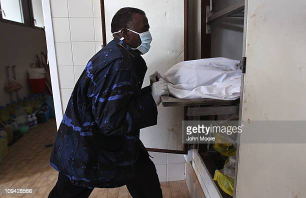 A hospital worker moves a victim of the violence in a morgue on February 25 2011 in Benghazi Libya Fighting has subsided around Benghazi in eastern...