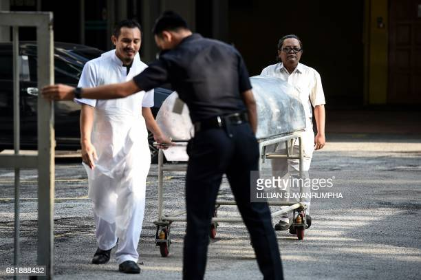 Hospital workers move a body cart through the gate of the forensics wing at the Hospital Kuala Lumpur where the body of Kim JongNam lies in Kuala...