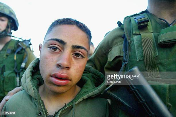 Hossam Abdo a 14 year old Palestinian boy is presented to the media while under arrest by Israeli soldiers at the army's checkpoint on March 24 2004...