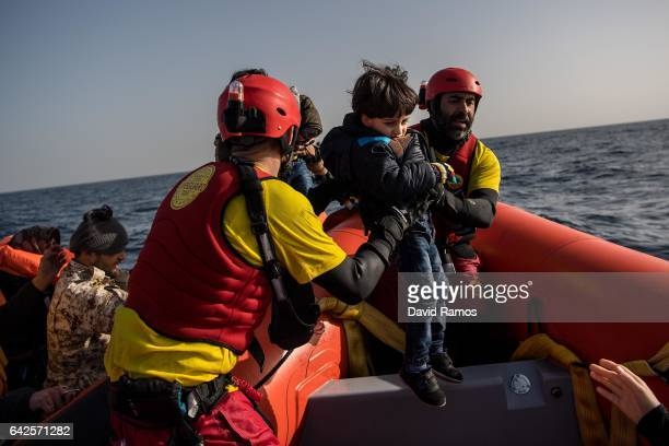 Hossia Mohamad of Syria is assisted by members of the Spanish NGO Proactiva Open Arms as he and his family are rescued from a wooden boat at 30 miles...