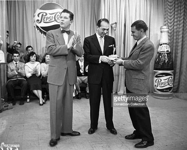 TV host and band leader Ted Steele presents a Cash Box Magazine award to band leader Percy Faith on the 'Ted Steele Show' with a man in front of...